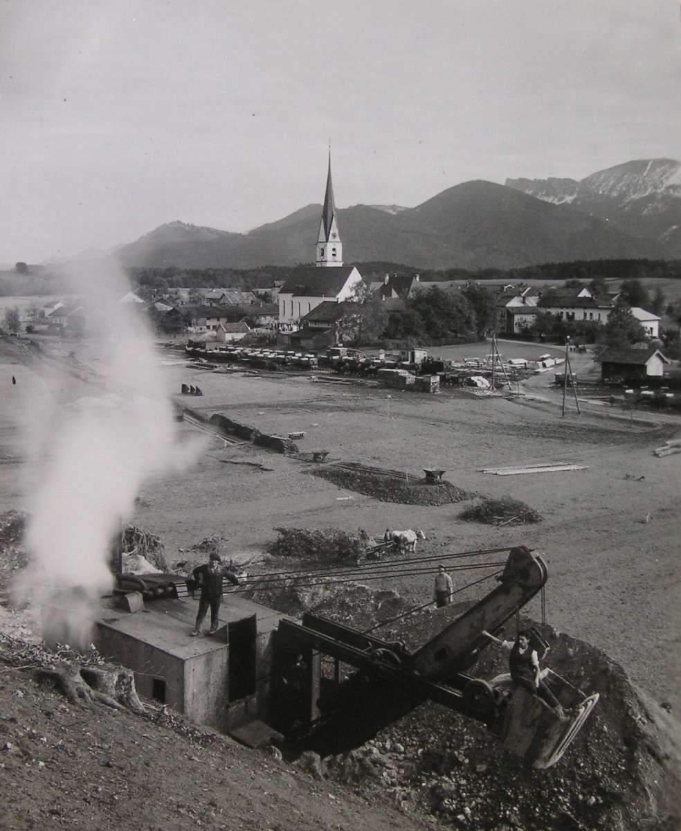 Altes Foto von einem Dorf mit einem Bagger im Vordergrund