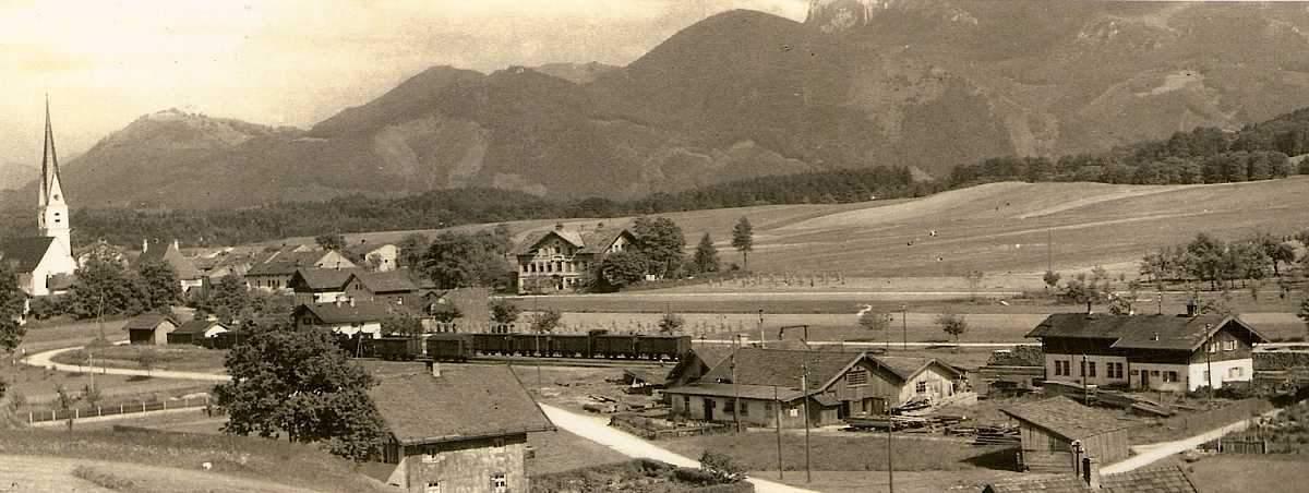 Altes Foto von einem Dorf mit Bergen im Hintergrund und Zug im Vordergrund