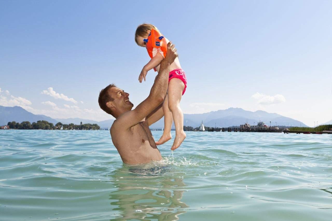 Vater badet im Chiemsee mit seinem Kind